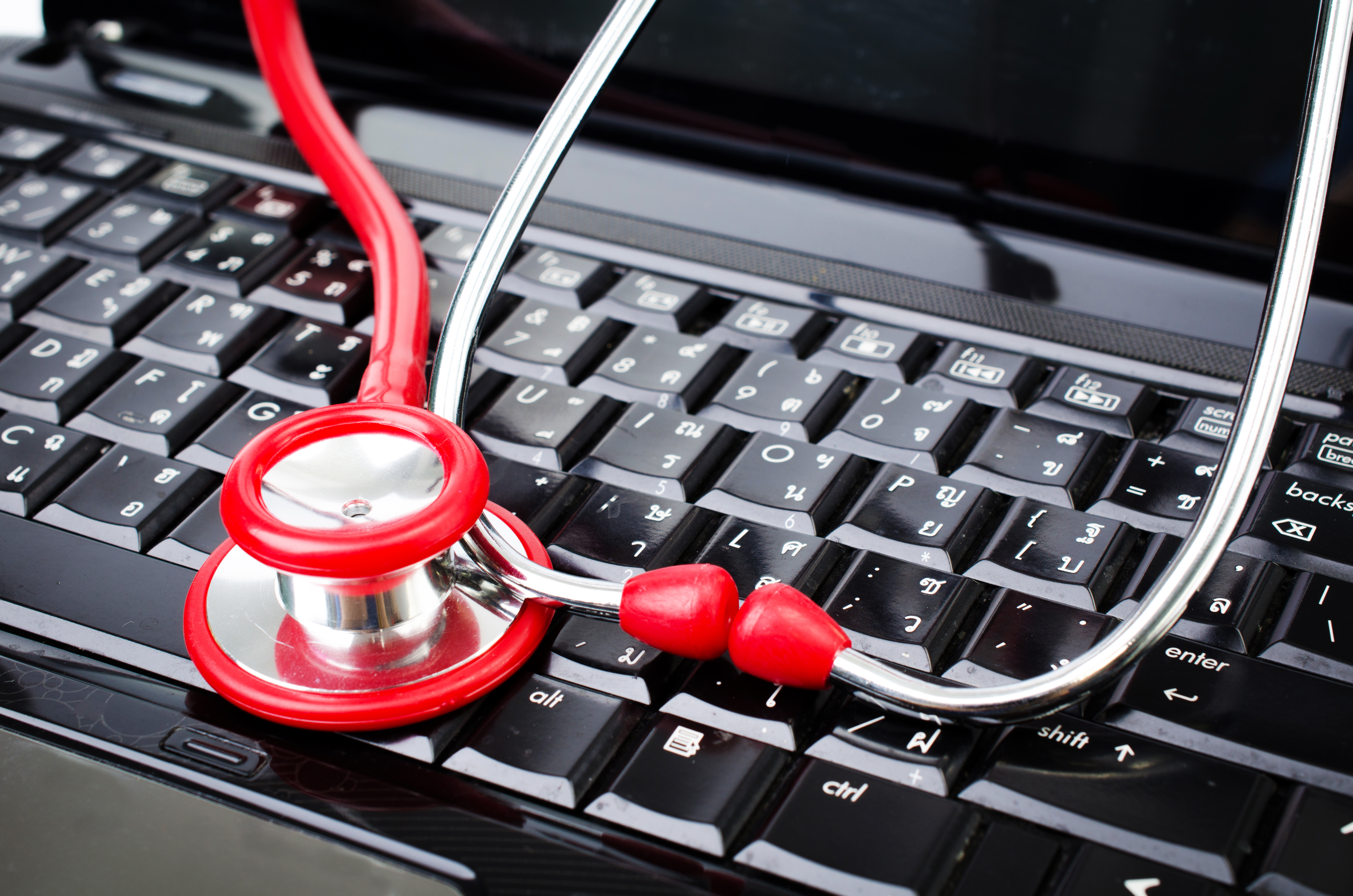 Red Stethoscope on labtop computer keyboard.
